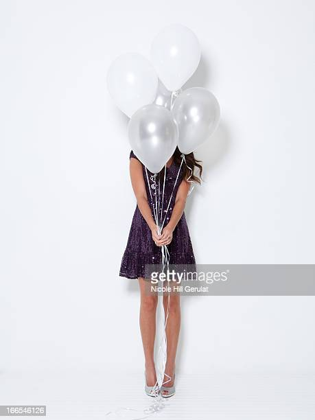 Young woman hiding behind balloons at party