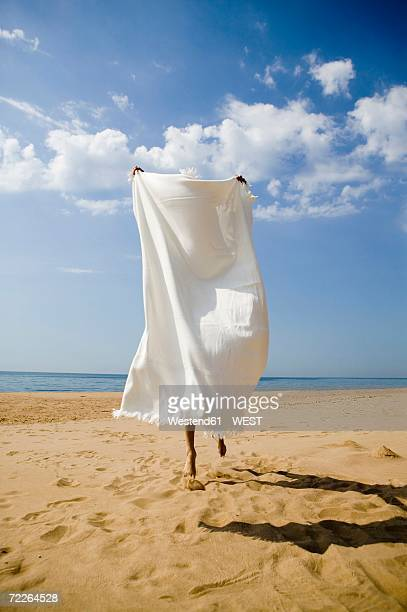Young woman hiding behind bath towel on beach