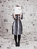 Young woman hiding face behind newspaper in newspapers covered room, studio shot