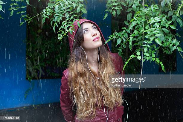 young woman hiding from rain, listening to music