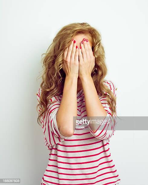 Junge Frau versteckt Ihr Gesicht mit Ihren Händen