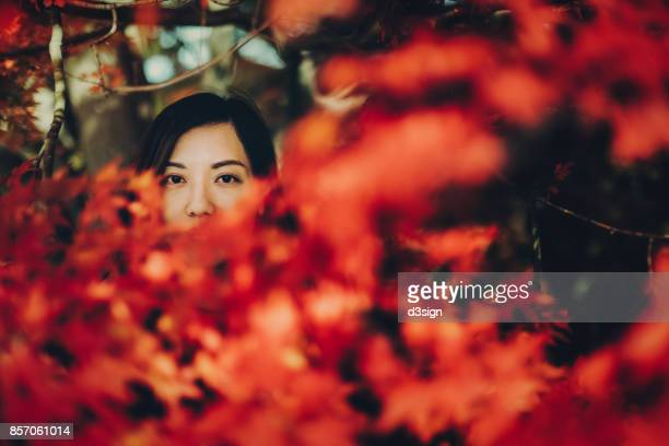 Young woman hiding in Japanese red maple leaves in park