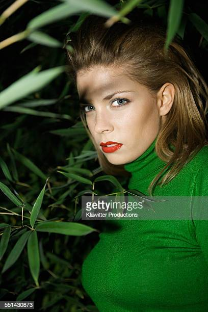 Young Woman Hiding in Leaves at Night