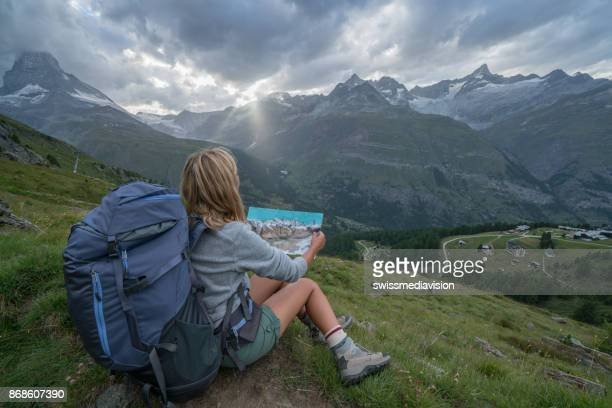 Young woman hiker looking at map on mountain trail, Matterhorn