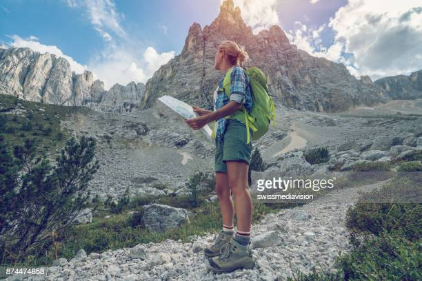 Young woman hiker looking at map on mountain trail