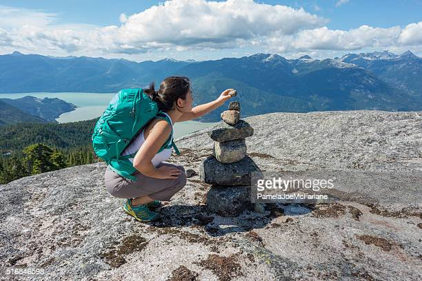 Young Woman Hiker Placing Rock on Cairn on Mountain Summit