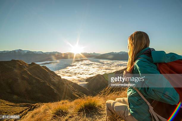 Young woman hiker relaxes on mountain peak above the clouds