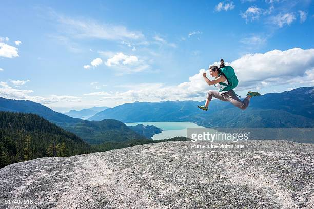 Young Woman Hiker with Backpack Jumping on Wilderness Mountaintop, Canada