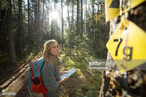 Jeune femme de randonnée en forêt à la recherche d'itinéraires sur la carte.
