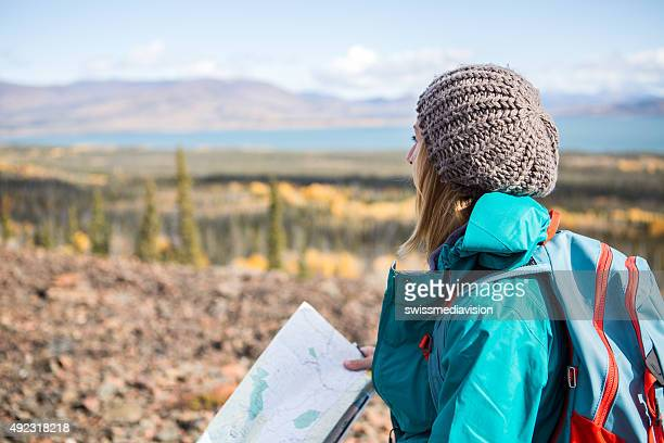 Young woman hiking looks for directions on map