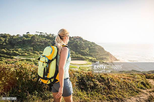Young woman hiking on coastal path, Erretegia beach, Bidart, France