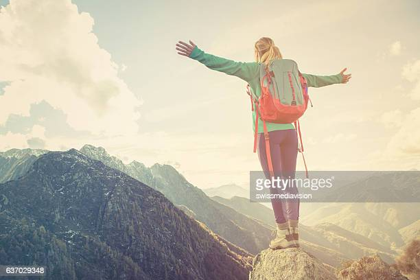 Young woman hiking reaches the mountain top, celebrates