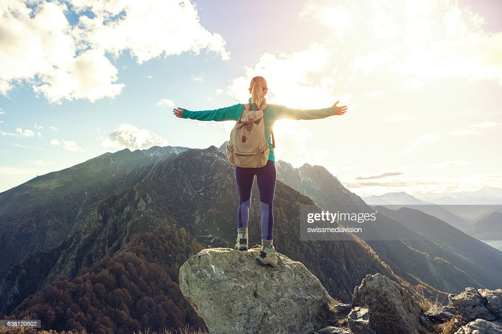 Young woman hiking reaches the mountain top, outstretches arms : Stock Photo