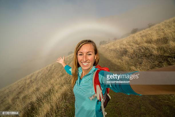 Young woman hiking takes selfie in the fog, rainbow