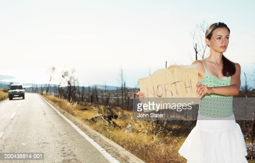 Young woman hitchhiking at side of road, holding up 'North' sign : Stock Photo