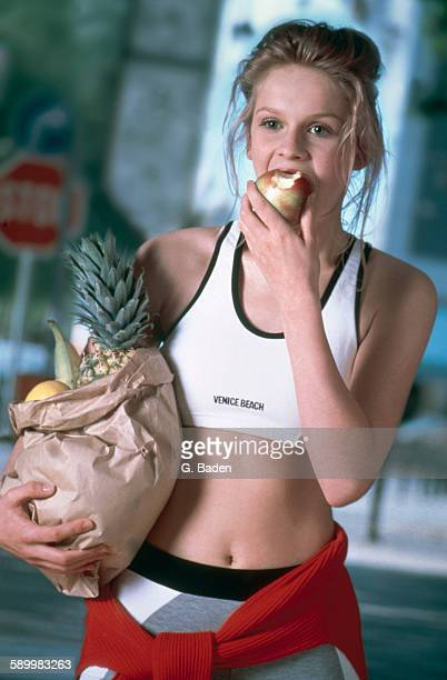 Young woman holding a bag with fruits