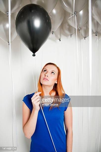 Young woman holding a black balloon