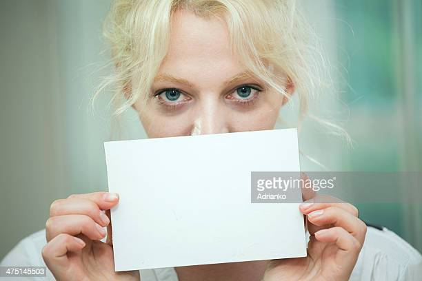 Young woman holding a blank card over her face