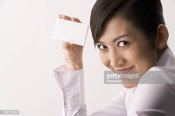 Young woman holding a blank credit card.