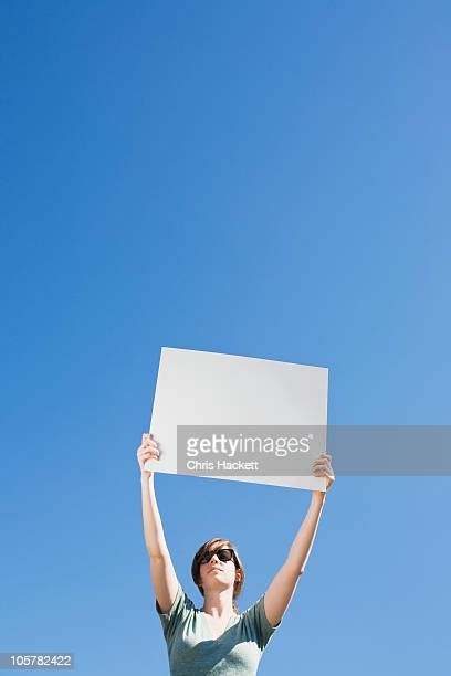Young woman holding a blank placard