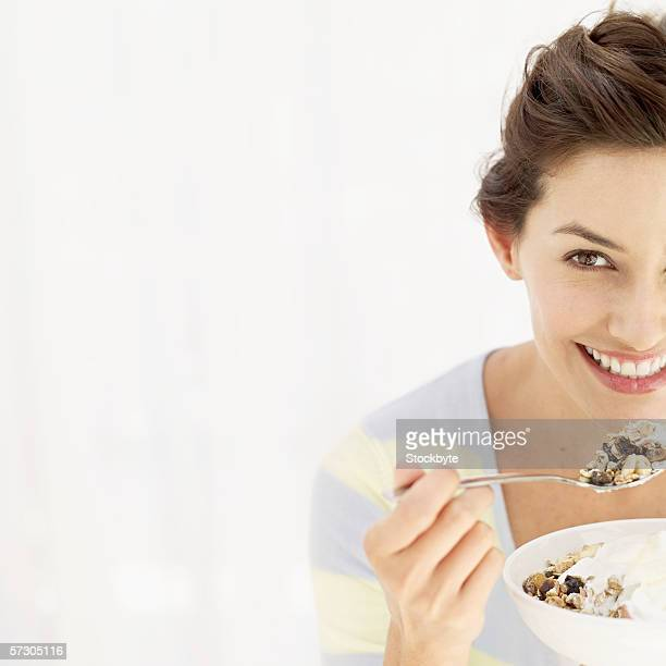 Young woman holding a bowl of cereal and a spoon