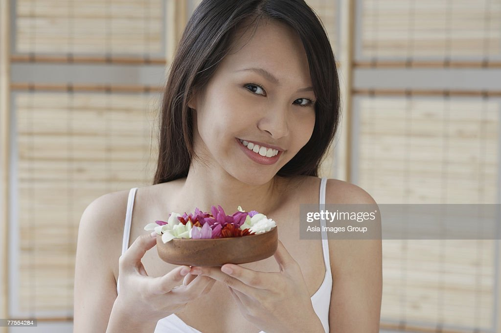 Young woman holding a bowl of flowers, smiling at camera : Stock Photo