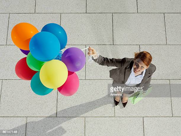 A young woman holding a bunch of balloons