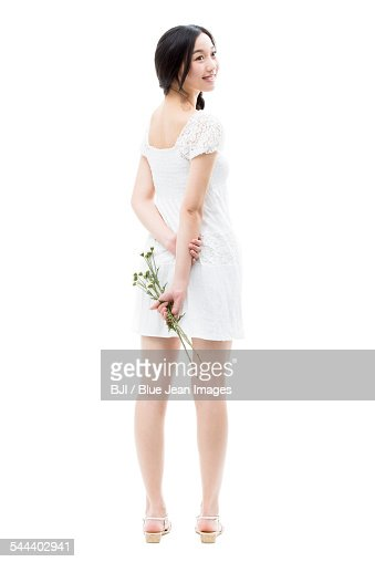 Young woman holding a bunch of flowers behind her back