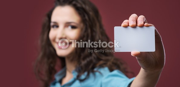 young woman holding a business card stock photo thinkstock