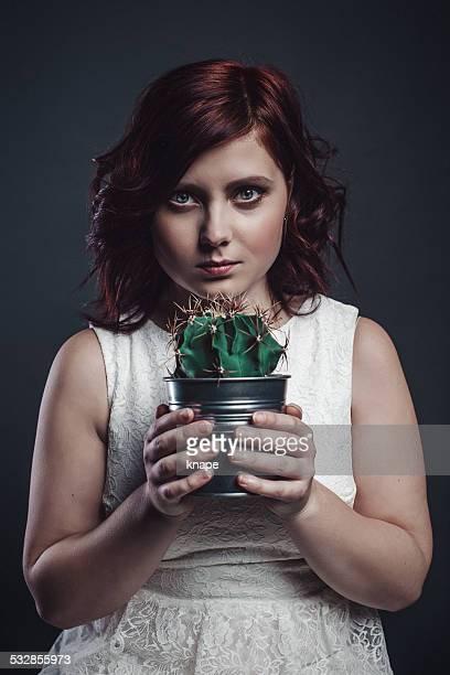 Junge Frau hält einen Kaktus mit einem unruhigen Gesicht