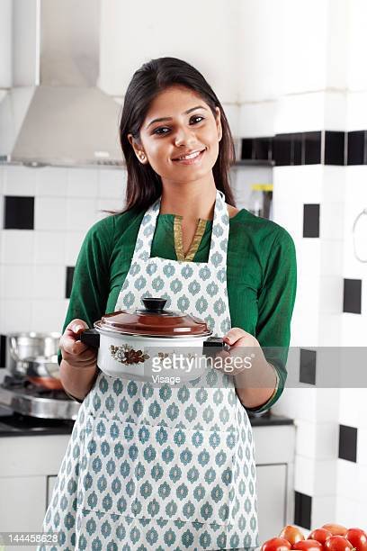 Young woman holding a casserole in a kitchen, Portrait, Smiling