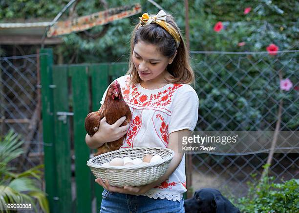 young woman holding a chicken and a basket of eggs