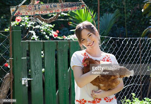 young woman holding a chicken