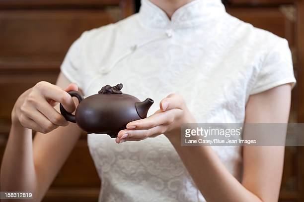 Young woman holding a Chinese boccaro teapot