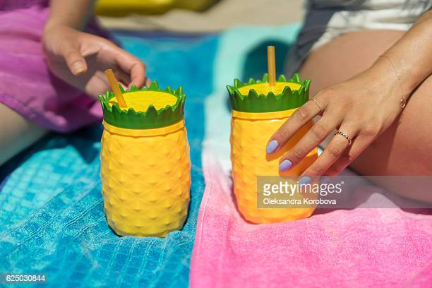 Young woman holding a colorful drink cup on a beach.