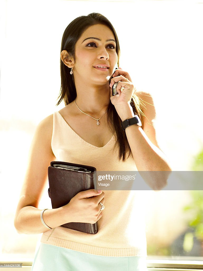A young woman holding a databook and using mobile phone : Stock Photo