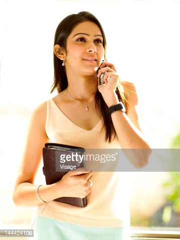 A young woman holding a databook and using mobile phone : Photo