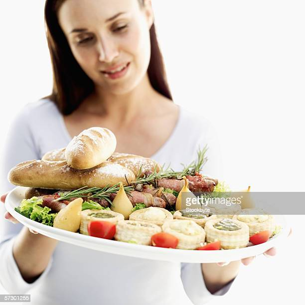 Young woman holding a dish of assorted vol-au-vents served with bread and bacon rolls