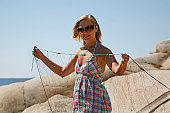 A young woman giving a helping hand making the fishing net ready for the next turn on a beautiful summer day in Norway.