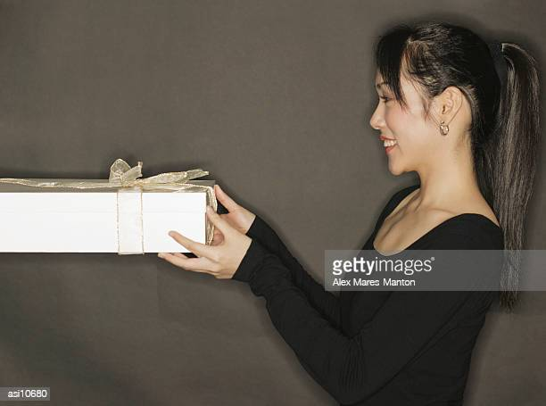 Young woman holding a gift, black background