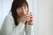 Young Woman Holding a Glass of Orange Juice, Side View