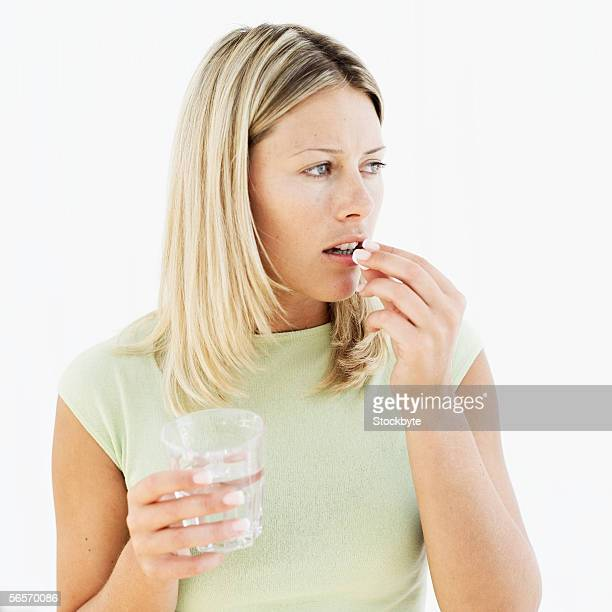 young woman holding a glass of water and taking a pill