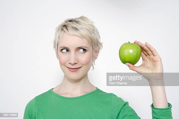 'Young woman holding a green apple, portrait'