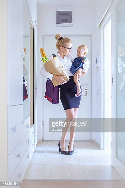 Young woman holding a grocery bag and her baby girl