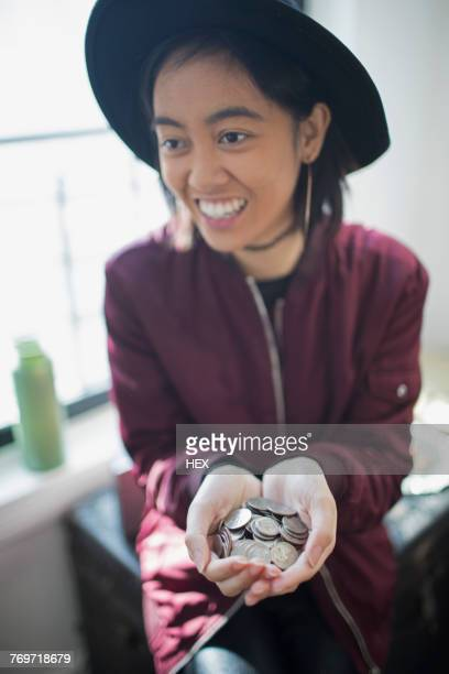 A young woman holding a handful of coins