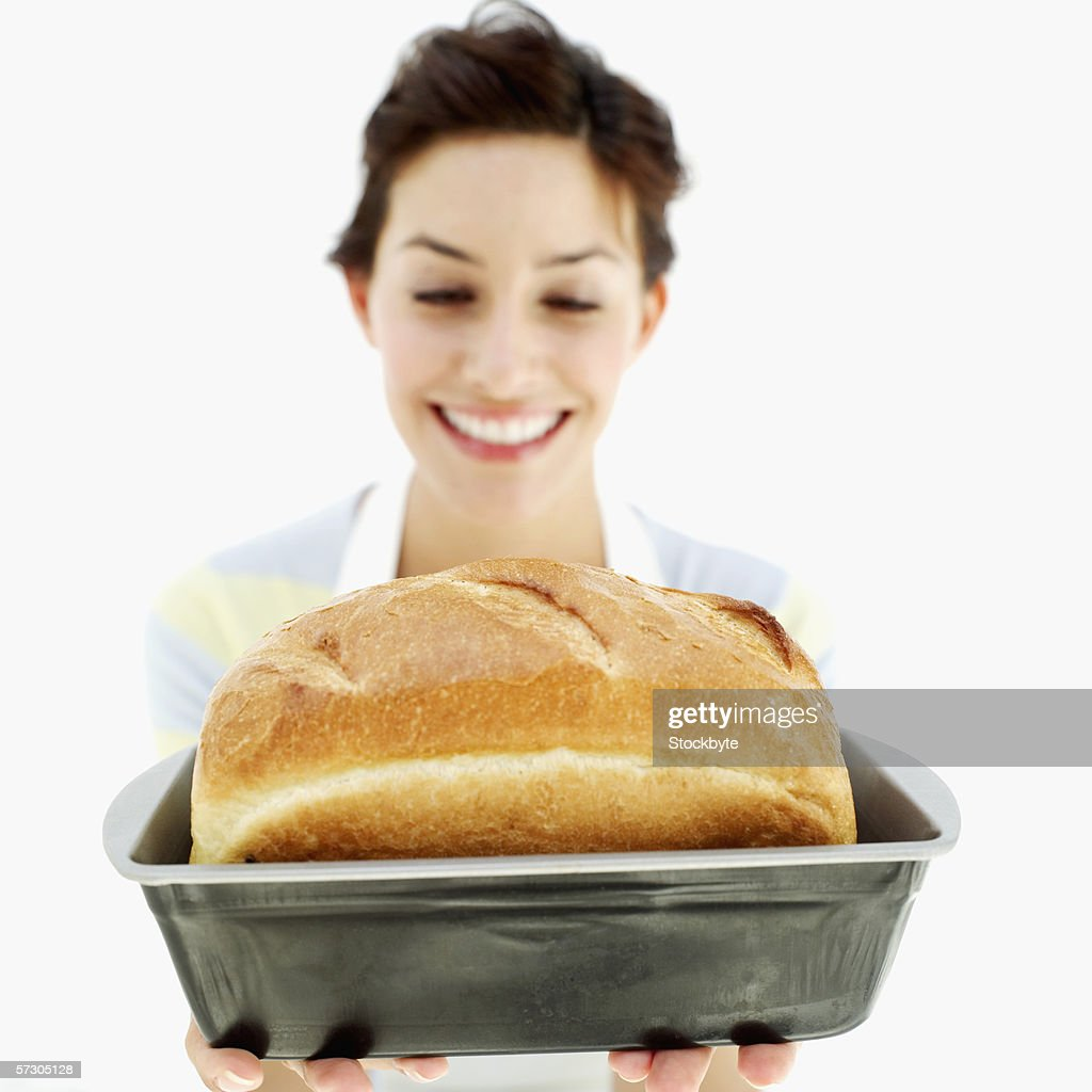 Young woman holding a loaf of freshly baked bread (blurred)