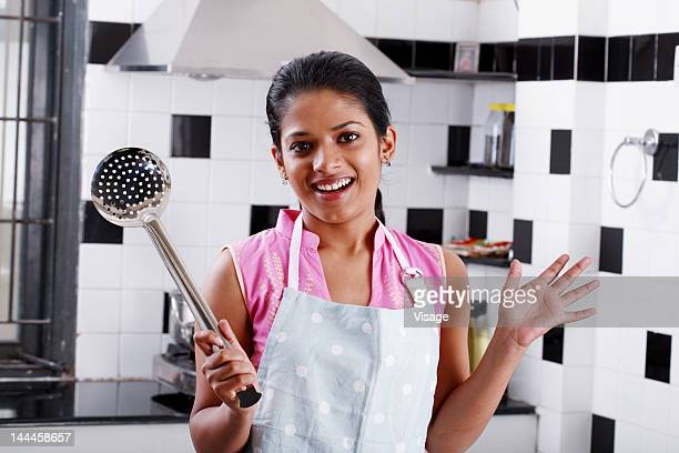 Young woman holding a metallic sieve in a kitchen