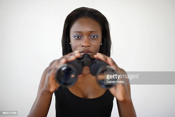 Young woman holding a pair of binoculars