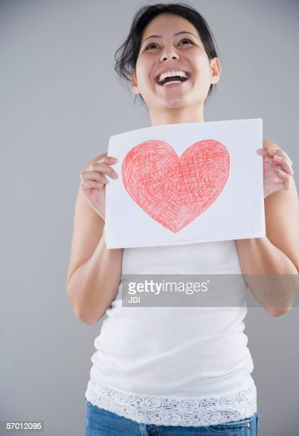 Young woman holding a piece of paper with a heart drawn on it