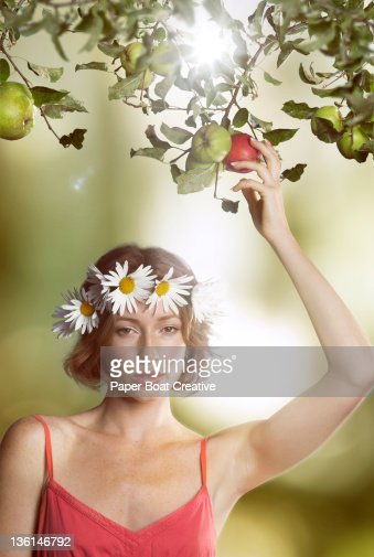 young woman holding a red apple in an orchard : Stock Photo